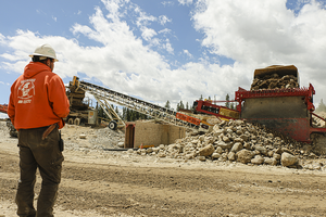 Trey Poulson watches as paydirt is dumped into a hopper loading a conveyor belt which feeds a wash plant.