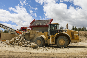 A loader hauls away rock and lost paydirt next to a hopper.