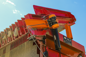 A Martin Engineering vibrator is mounted to a grizzly screen on a hopper.